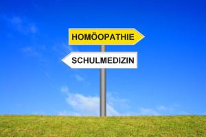 Schild Wegweiser zeigt in zwei Richtungen: Homöopathie oder Schulmedizin